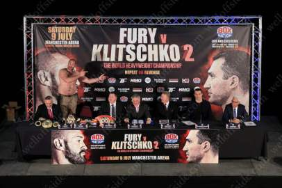 Boxer Tyson Fury points towards his opposite number, Wladimir Klitschko (2R), during a press conference to preview their upcoming title fight in Manchester