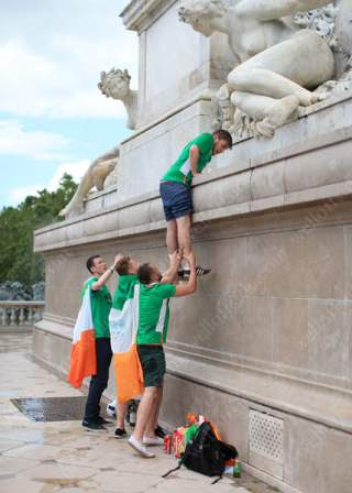 Fans help a friend up onto the Monument aux Girondins