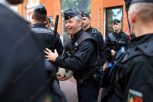 The senior Gendarmerie officer releases the football to the fans again