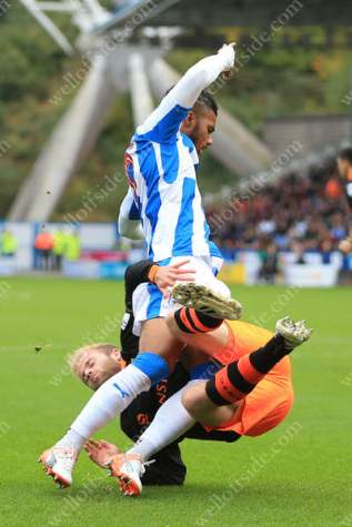 Barry Bannan of Sheff Wed tangles with Elias Kachunga of Huddersfield
