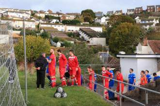 Teignmouth and Brixham players walk out onto the pitch at Coombe Valley