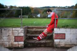 A Teignmouth player enjoys a post-match cigarette as he flicks through his mobile phone after the game