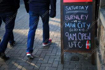 A blackboard outside a pub advertises Burnley's match against Man City, as fans walk to the game