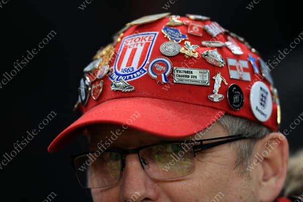 Souvenir pins and badges on a Stoke fan's cap