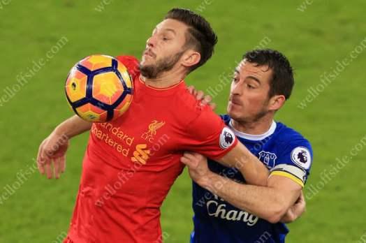 Adam Lallana of Liverpool battles with Leighton Baines of Everton
