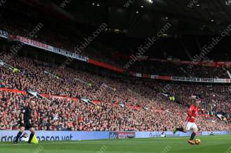 Only the linesman stands between Wayne Rooney and the Man Utd fans inside Old Trafford