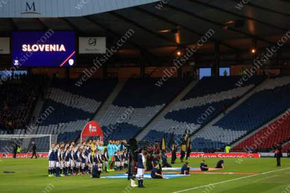 Scotland players line up before their FIFA World Cup Qualifying match against Slovenia in front of hoards of empty seats inside Hampden Park