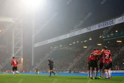 Man Utd players celebrate their late winner in the rain at Ewood Park