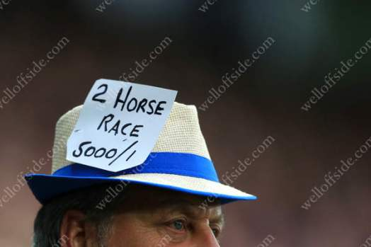 A Leicester fan taunts the visitors with a 5000/1 sign on his hat. Spurs fans were known to call the title chase a 'two-horse race', neither of which referred to Leicester, who eventually won it