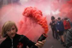 Liverpool fans carry a red flare through the streets
