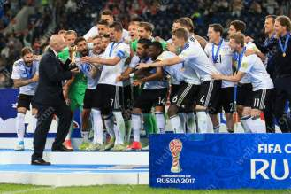 Germany players build the moment as FIFA President Gianni Infantino hands the trophy to captain Julian Draxler