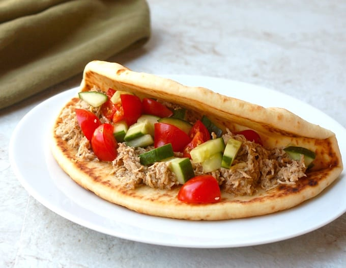Greek chicken pita sandwich with chopped cucumber and tomatoes on white plate.