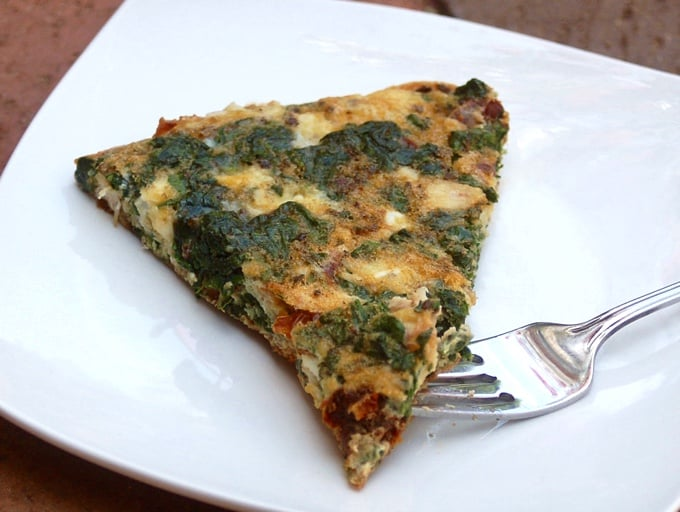 Wedge of Greek Frittata with Spinach and Feta on white plate with fork.