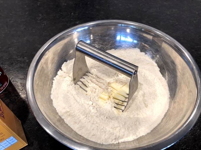 Using pastry blender to cut butter with flour in mixing bowl