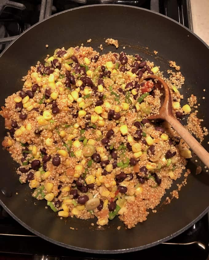Cooking quinoa, black beans, corn, green onions with salsa in skillet.