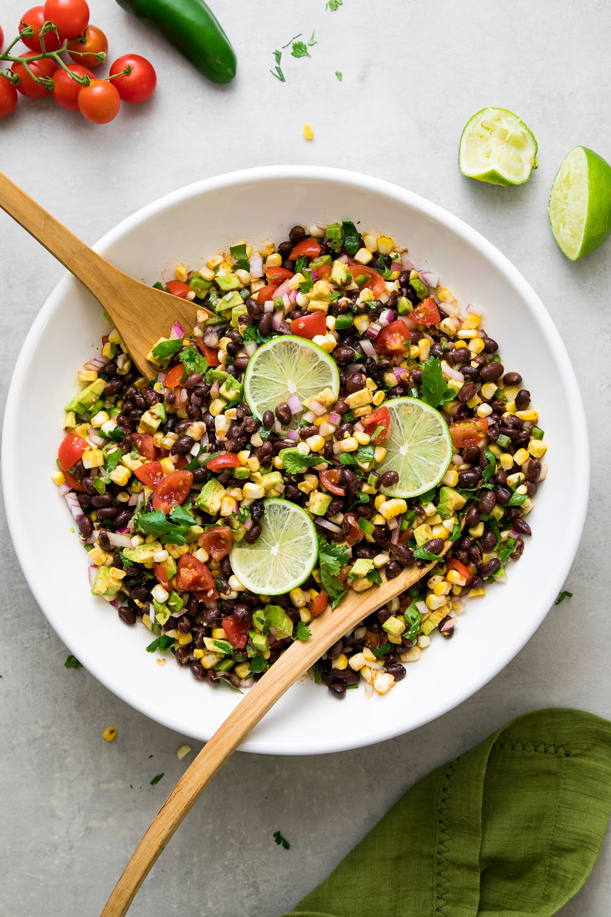 top down view of freshly mixed black bean corn salad in a large white bowl with wooden salad utensils.