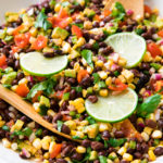 side angle view of black bean corn salad in a white bowl.