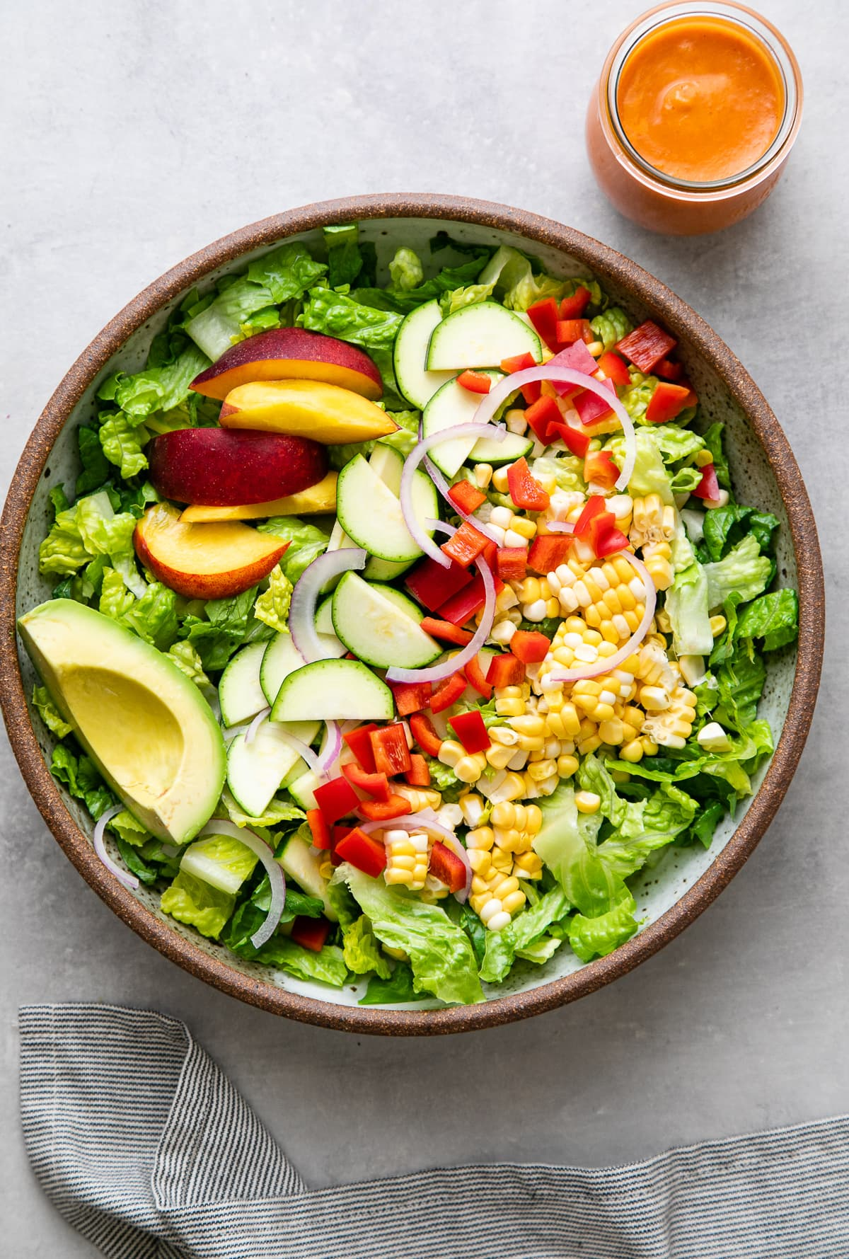 top down view of healthy farmer's market salad in a bowl with dressing on the side in glass jar.