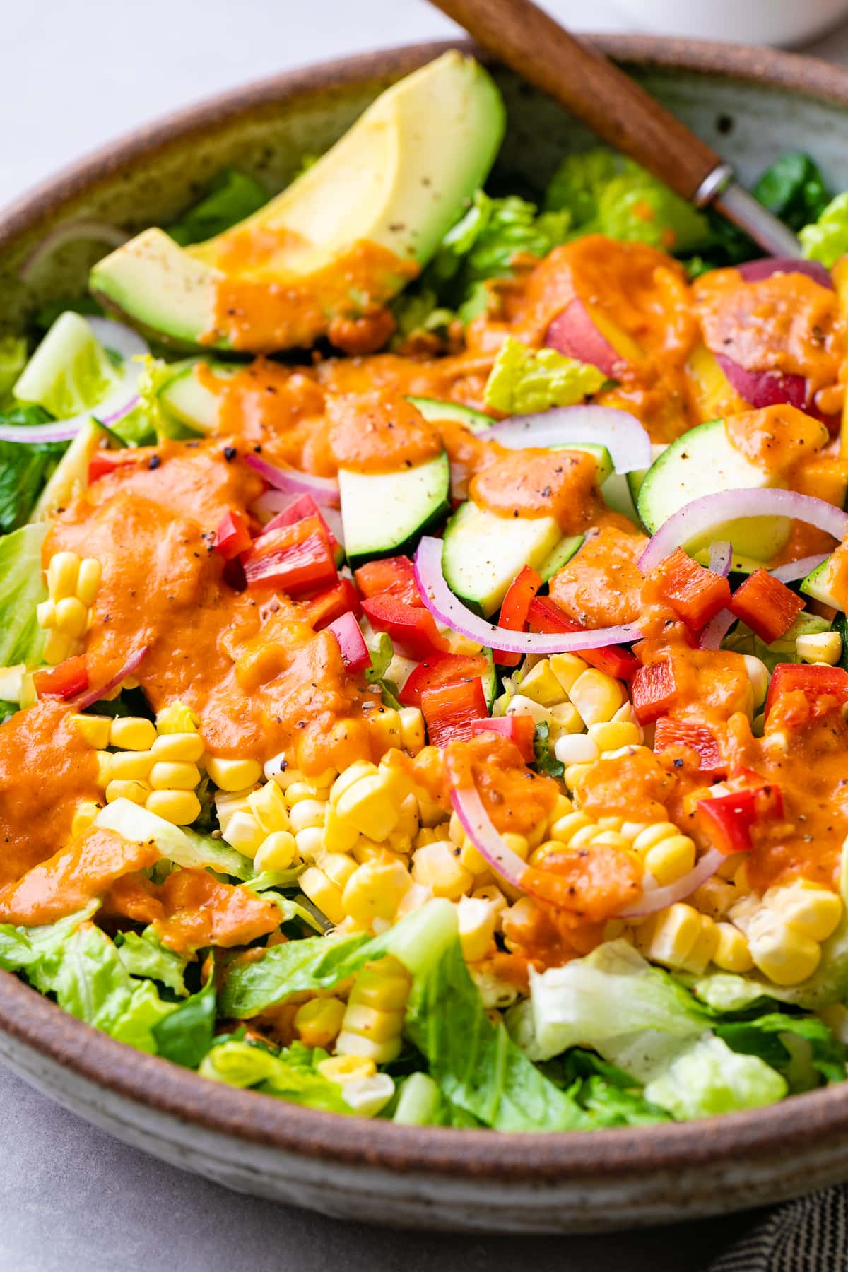 up close, side angle view of healthy farmer's market salad with sun-dried tomato vinaigrette in a bowl.