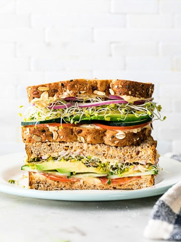 head on view of healthy hummus veggie sandwich sliced in half and stacked.