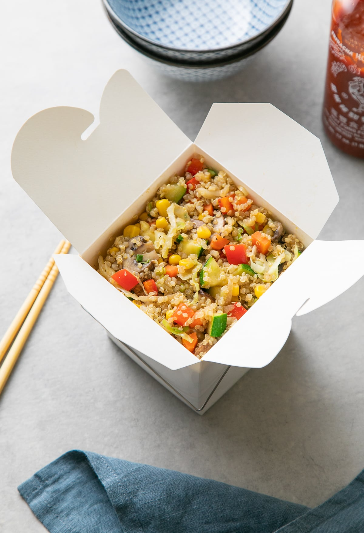 vegetable quinoa fried rice in a chinese take out box with items surrounding.