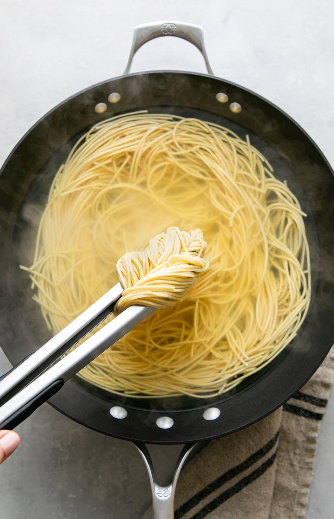 top down view of cooked ramen noodles between tongs.