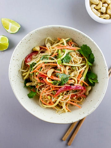 top down view of raw pad thai in a bowl with items surrouding.