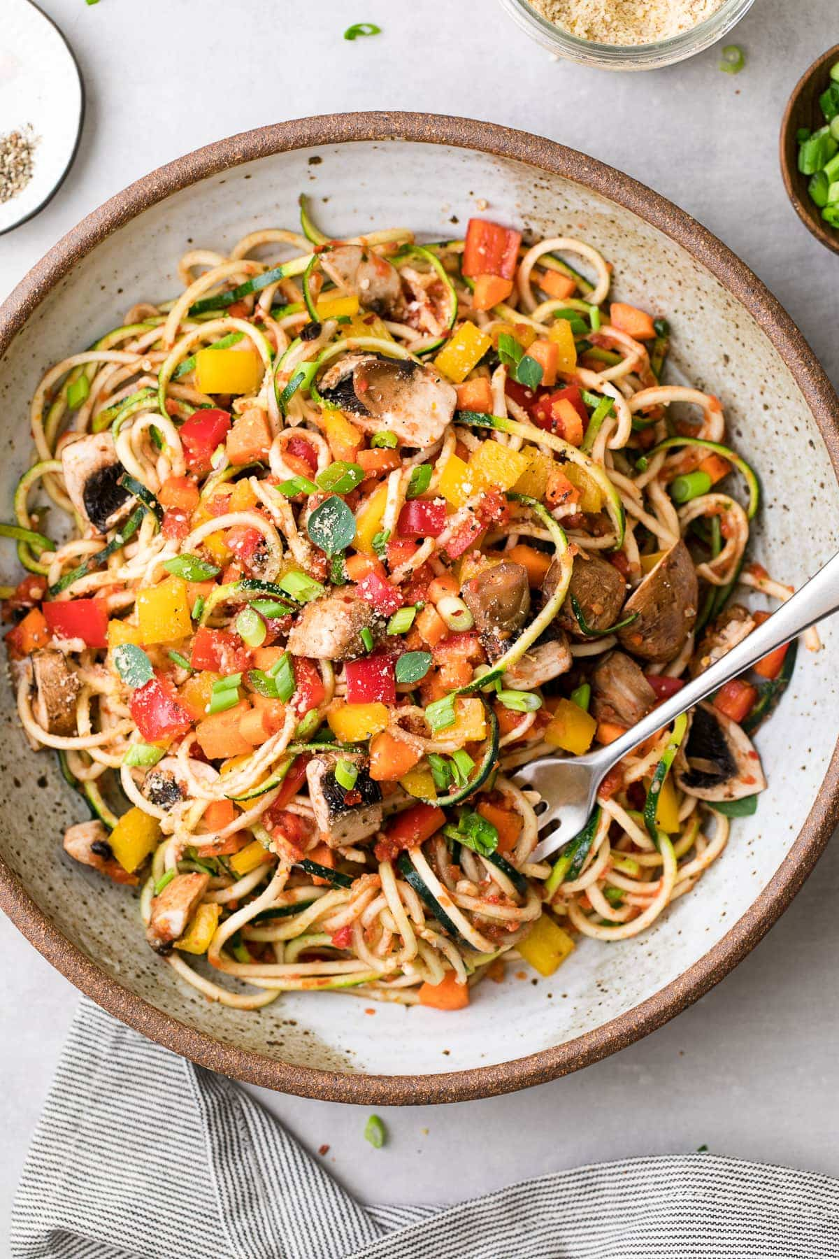 top down view of plated raw spaghetti + vegetable pasta with items surrounding.