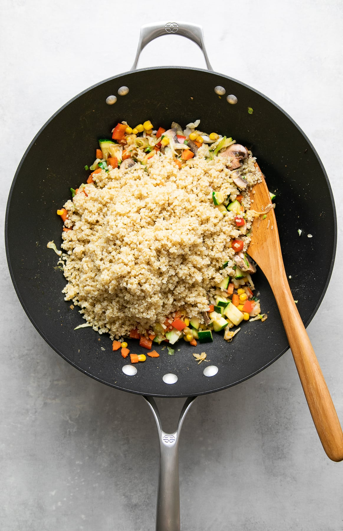 top down view of quinoa added to stir fried veggies to make quinoa fried rice.