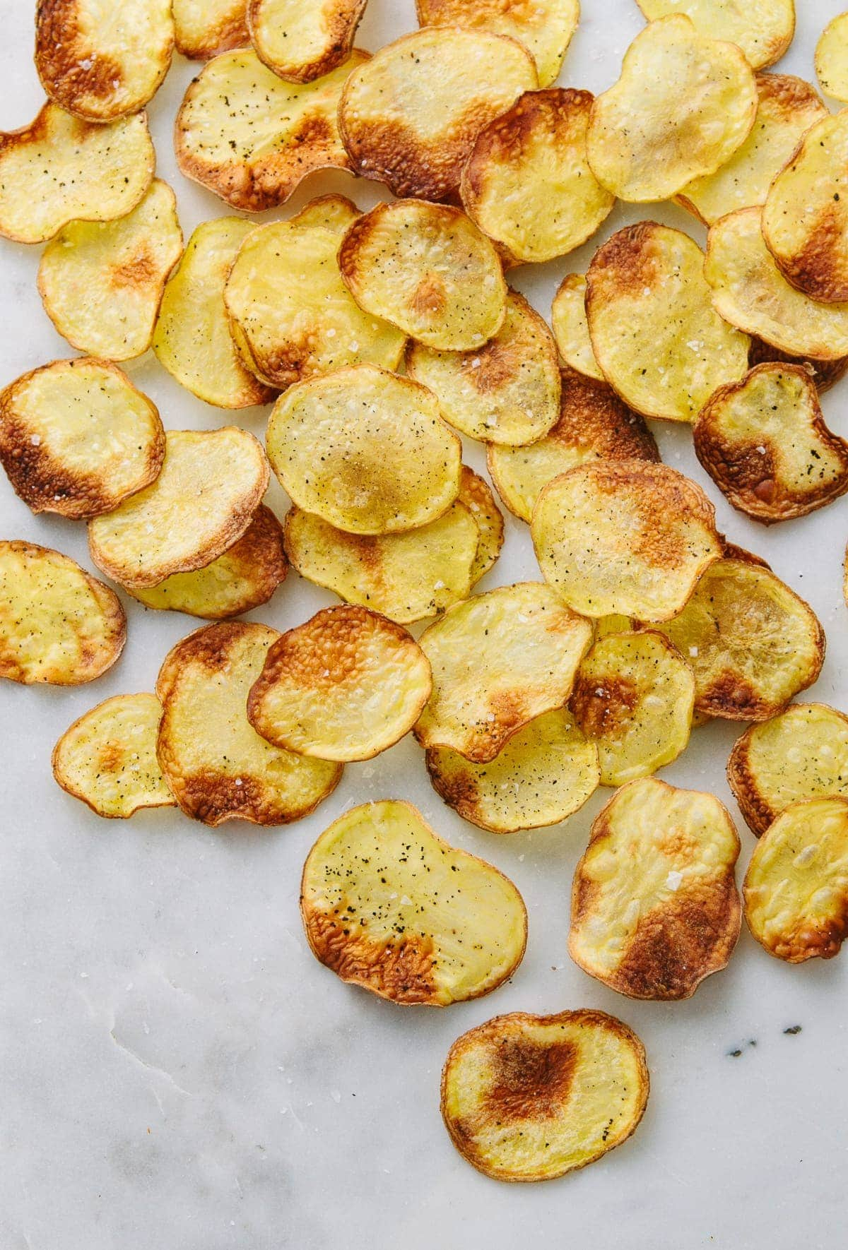 top down view of scattered homemade potato chips on a marble slab.