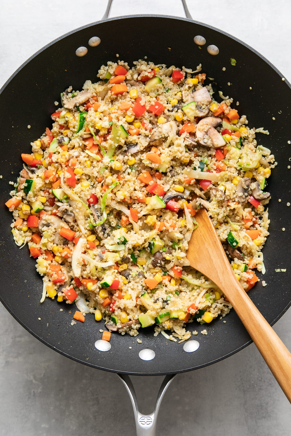top down view of freshly made quinoa fried rice in a wok with wooden spoon.