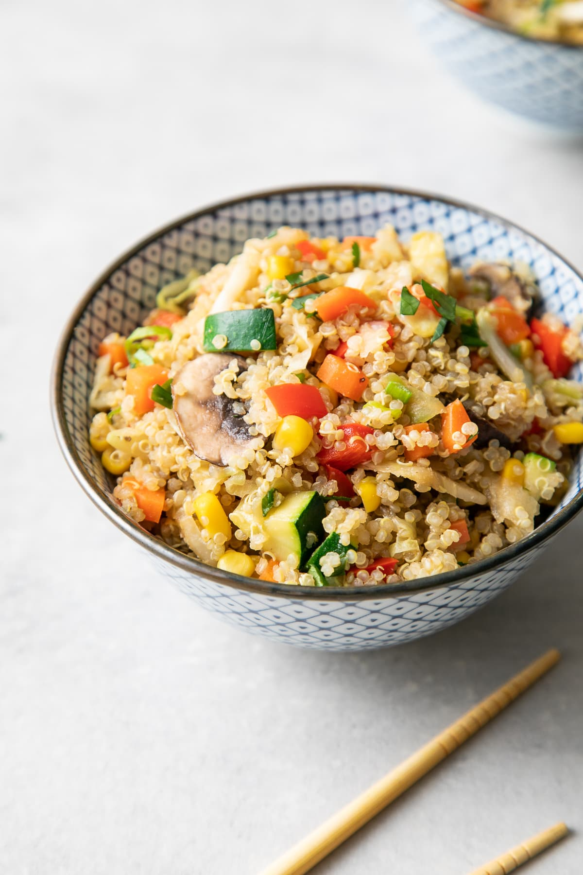 side angle view of blue and white bowl with vegetable quinoa fried rice.