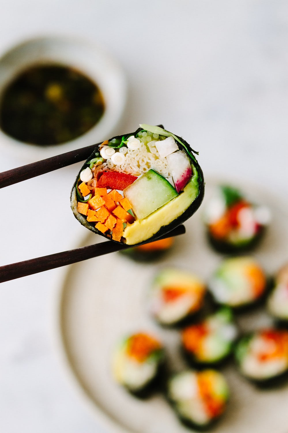 side angle shot of a slice of raw vegan sushi roll between 2 chopsticks