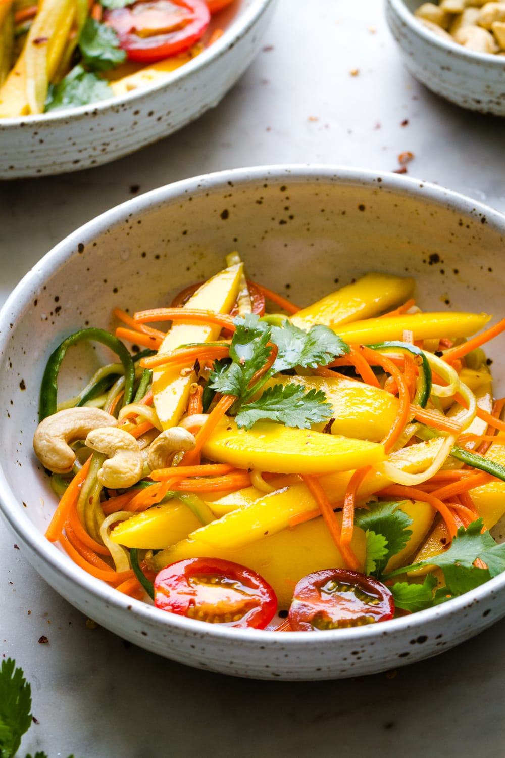 side angle view of bowl with a serving of spicy thai mango salad