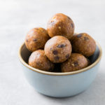 side angle view of chocolate chip energy bites in a small bowl.