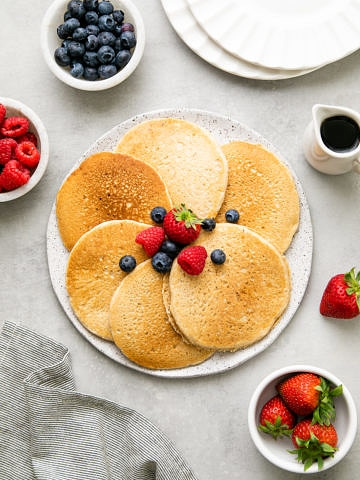 top down view of vegan pancakes on a plate and topped with fruit and items surrounding.