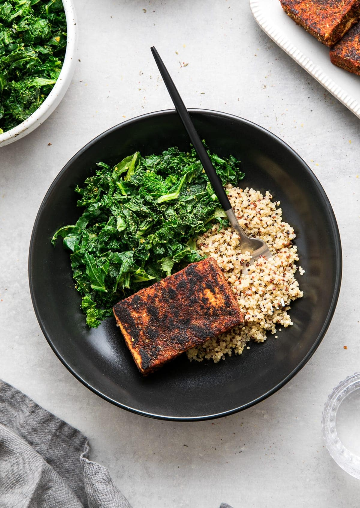 top down view of a black bowl with blackened tofu, sauteed kale and quinoa.
