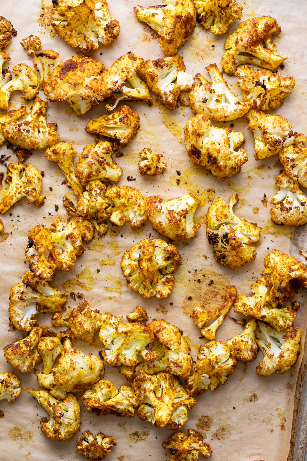 top down view of roasted cauliflower with curry and sriracha on a baking sheet just pulled from the oven.
