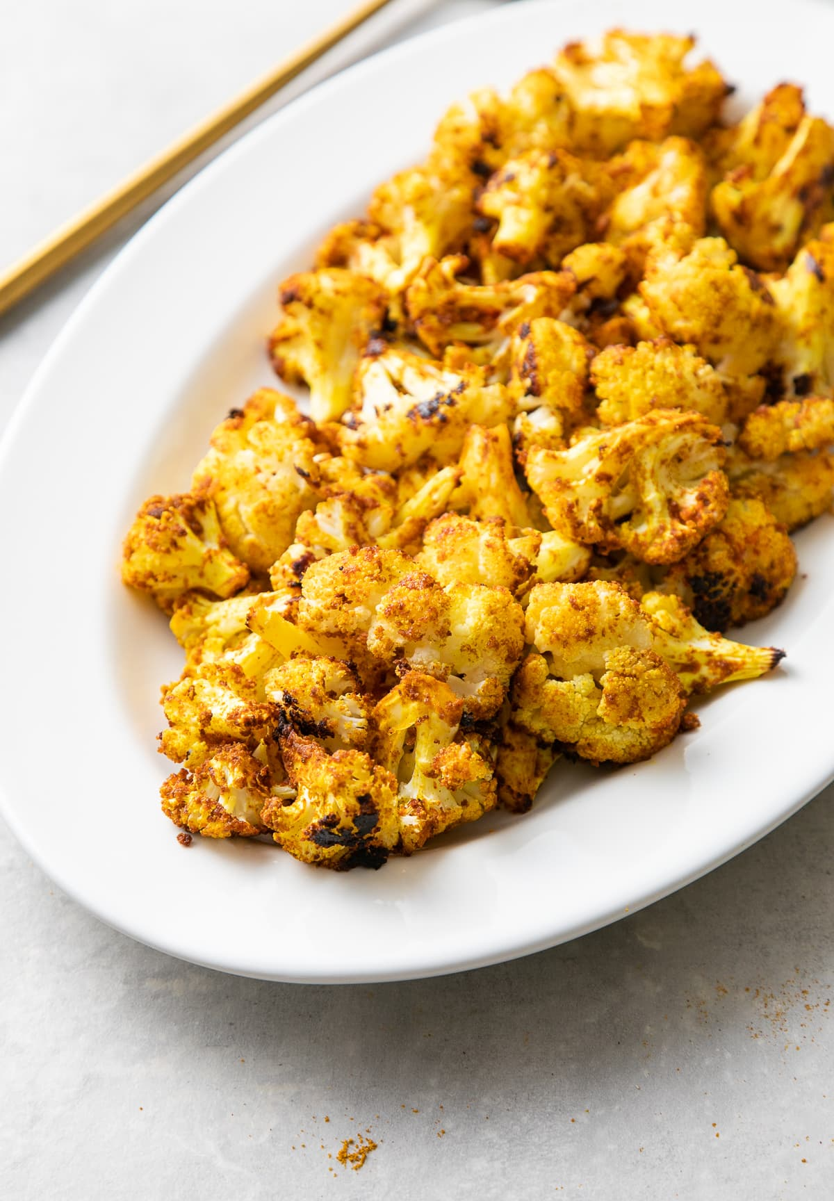 side angle view of a serving platter with freshly made curry sriracha roasted cauliflower.