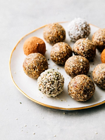 side angle view of healthy no bake hemp heart and oat energy bites on a small plate.