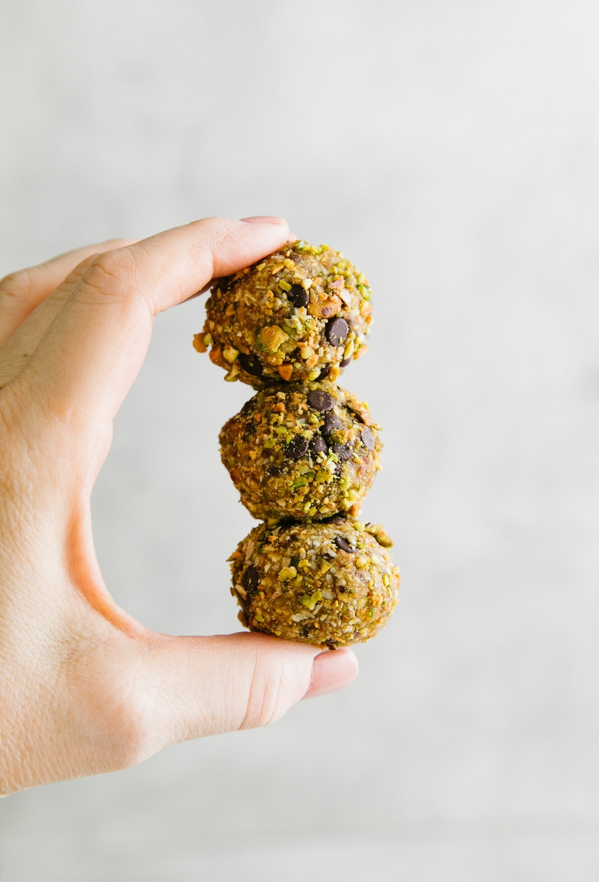 head on shot of fingers holding 3 no bake cookie balls.