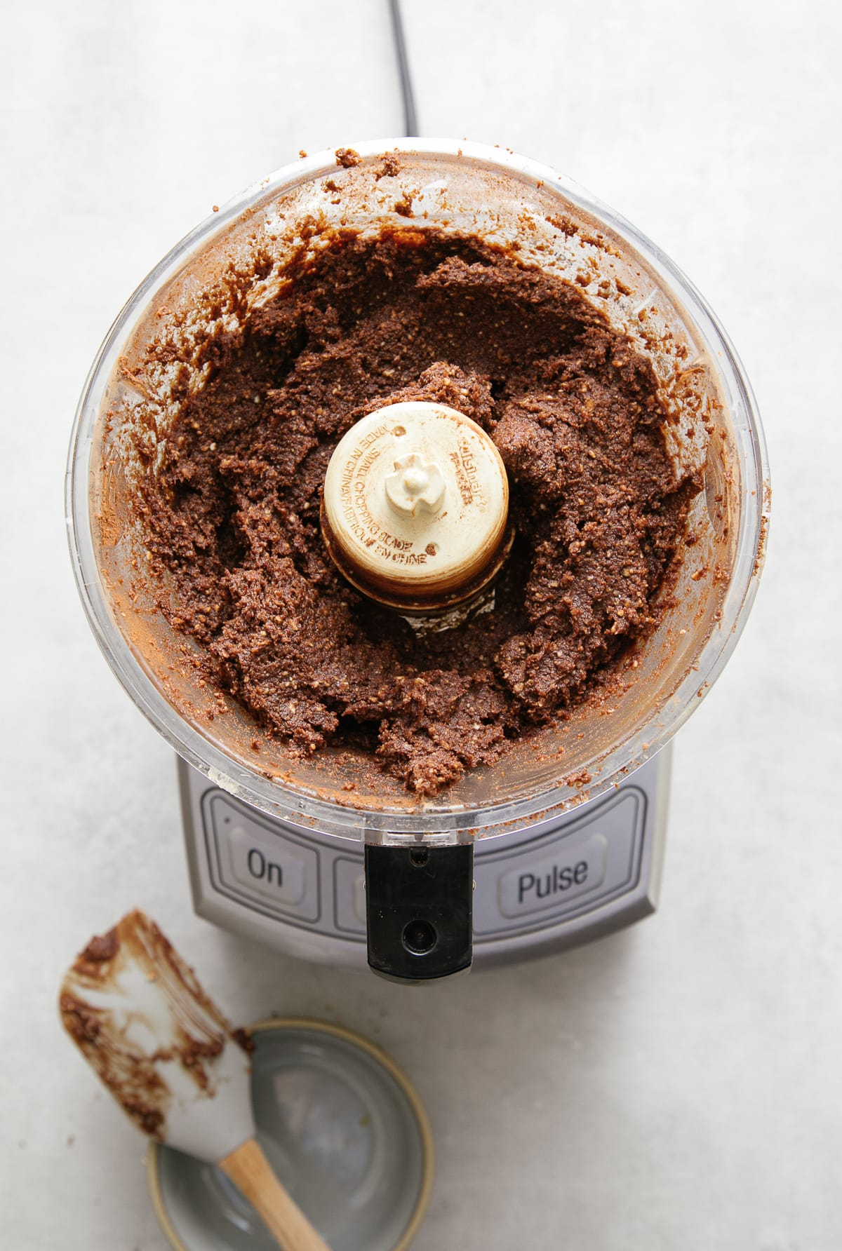 top down view of raw vegan coconut brownie dough in food processor.