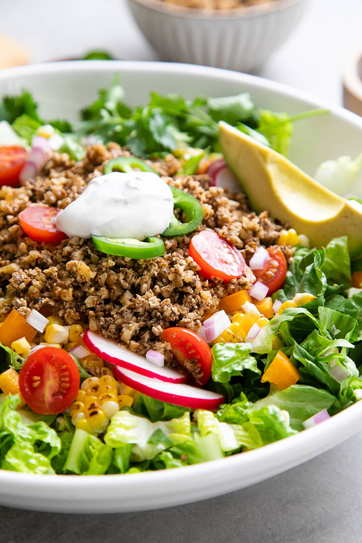 side angle view of healthy taco salad in a white bowl.