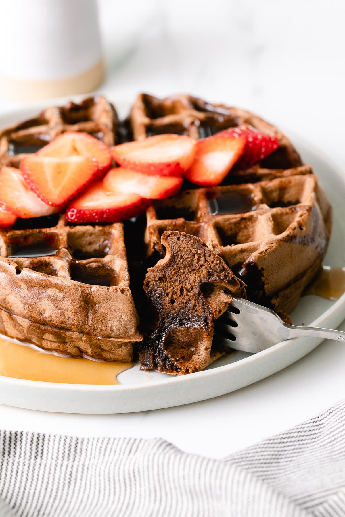 head on view of vegan chocolate belgian waffle on a plate with slice cut.
