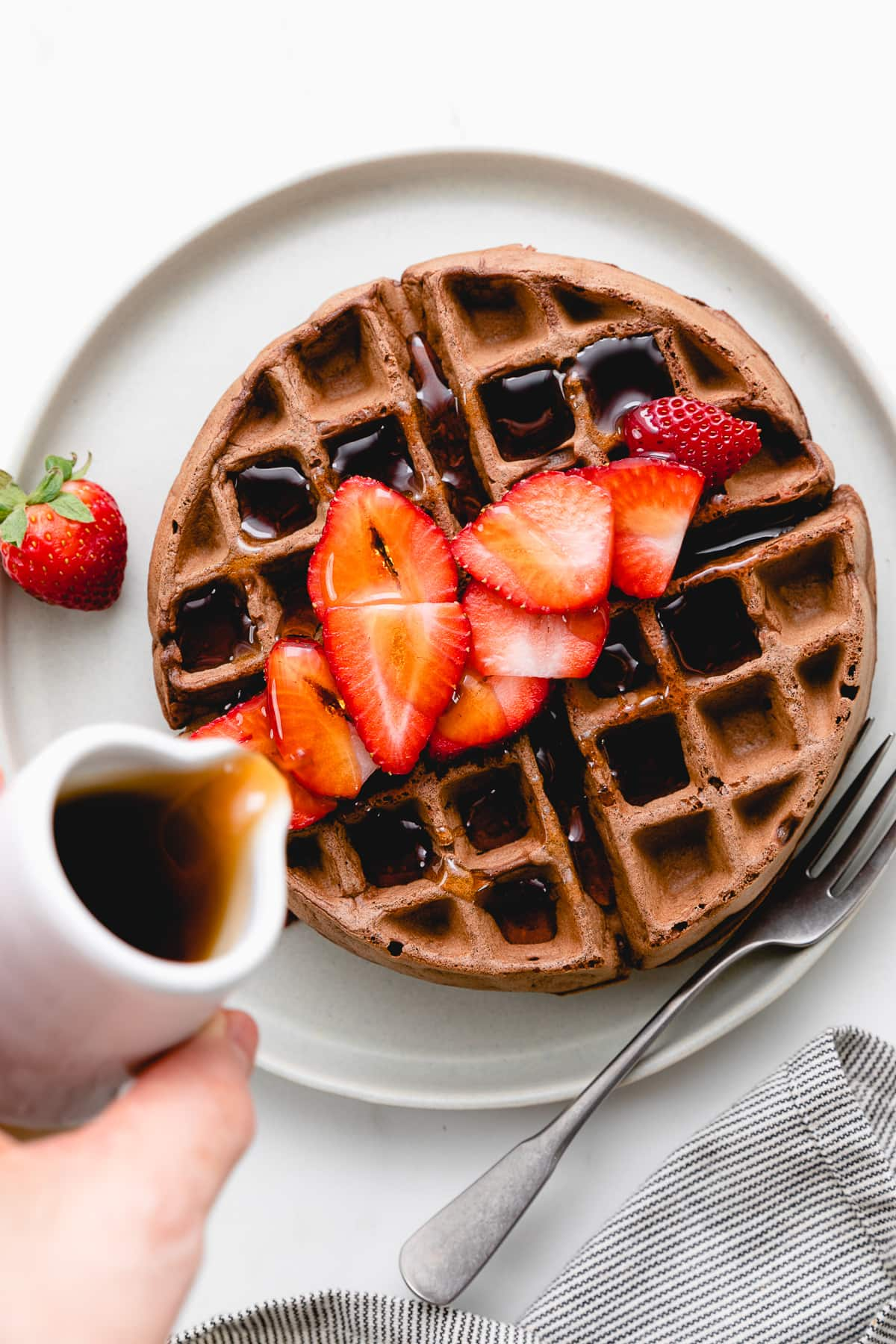 top down view of healthy vegan chocolate belgian waffle on a plate with syrup being poured overtop.