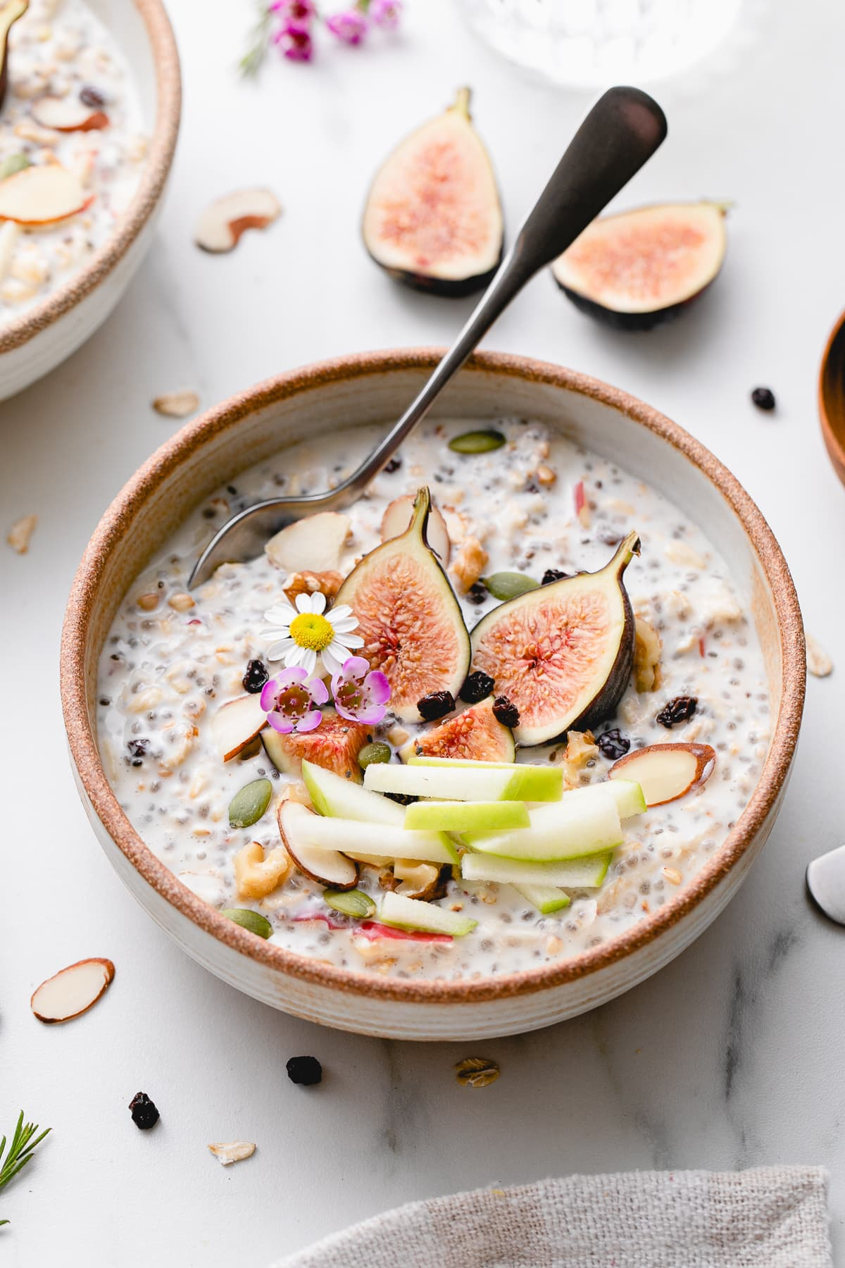 side angle view of bowl of bircher muesli with fruits and nuts with items surrounding.