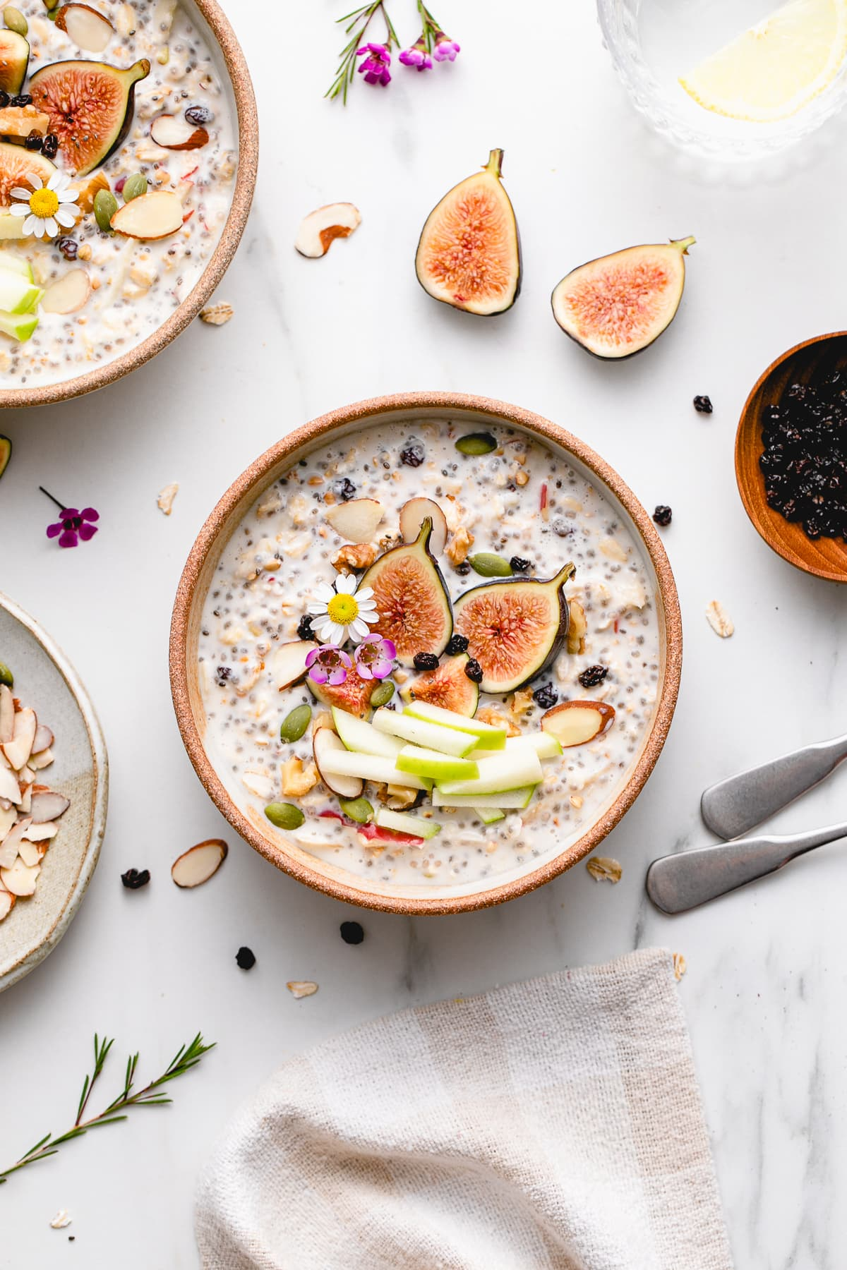 top down view of bowl of bircher muesli with fruits and nuts with items surrounding.