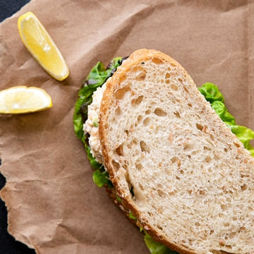 top down view of sandwich on brown paper with lemon wedges.