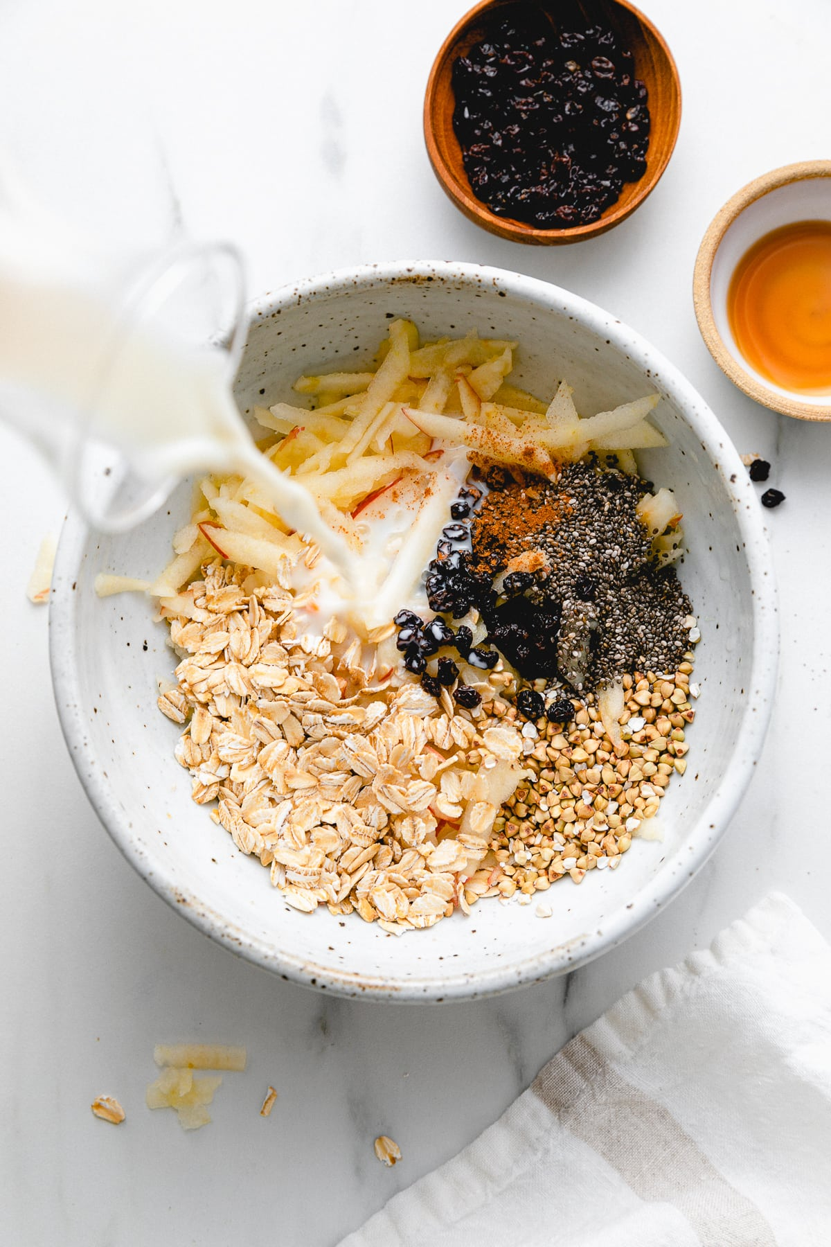 top down view showing the process of making healthy bircher muesli in a bowl.