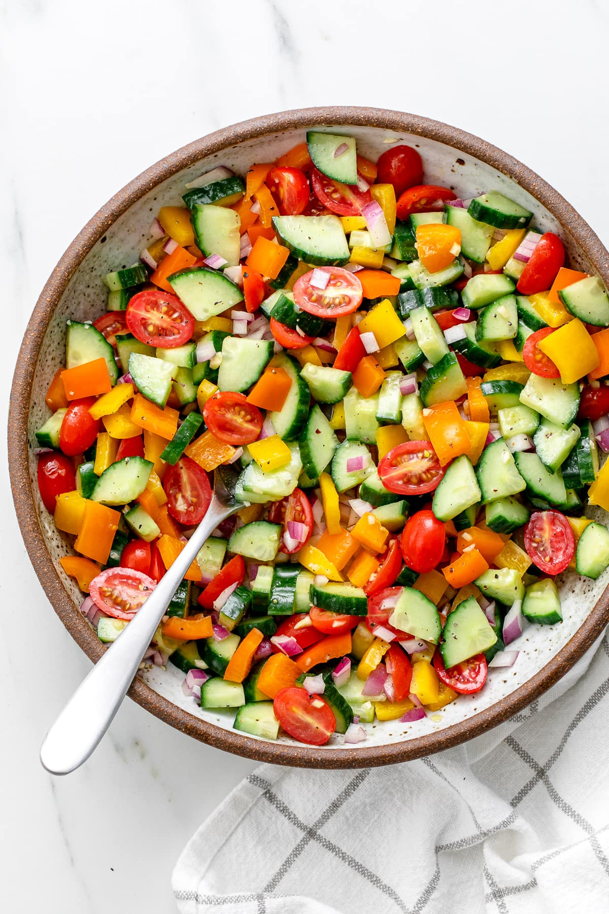 top down view of freshly made vegetable salad in a bowl with serving spoon.